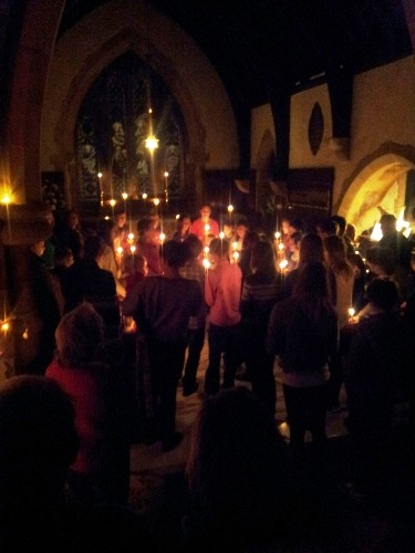 The Christingles are all lit in the darkened Church and the children sing 'Away in a Manger'