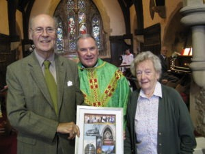 Bishop John and Edna receive a framed photograph from the Rector as a memento of their time at St Ninian's