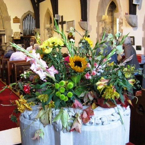 Floral display in the Font - people arriving for the Harvest Festival Service